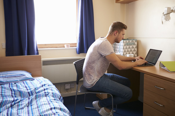 Male Student Working In Bedroom Of Campus Accommodation